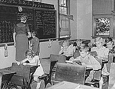 In this photo of an old, one-room classroom in Grundy, Iowa, the 7-year-old boy getting help at the blackboard is the only second-grader in the class.